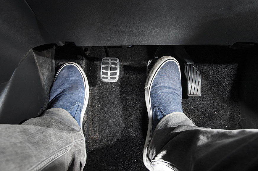 Lift the right foot from the accelerator and press the brake pedal.